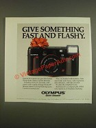 1985 Olympus Quick Shooter Camera Ad - Give something fast and flashy